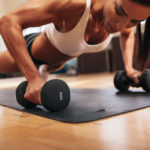 muscular-woman-doing-push-ups-on-dumbbells-in-gym-1